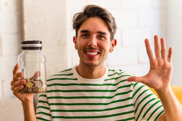 Jonge gemengd ras man met spaarvarken in zijn woonkamer glimlachend vrolijk met nummer vijf met vingers.