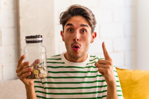 Jonge gemengd ras man met spaarvarken in zijn woonkamer met een geweldig idee, concept van creativiteit.