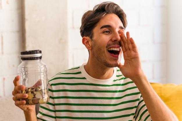 Jonge gemengd ras man met spaarvarken in zijn woonkamer schreeuwen en handpalm in de buurt van geopende mond houden.
