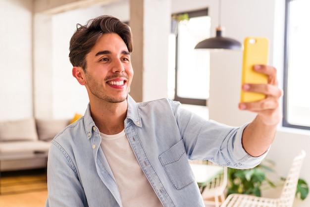 Jonge gemengd ras man praten aan de telefoon in een keuken