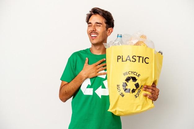 Jonge gemengd ras man recycling van plastic geïsoleerd op gele achtergrond lacht hardop met de hand op de borst.