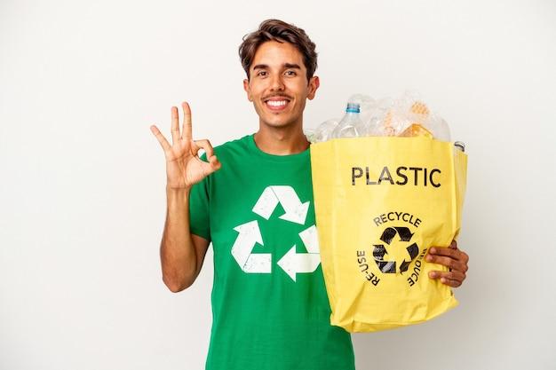 Jonge gemengd ras man recycling van plastic geïsoleerd op gele achtergrond vrolijk en zelfverzekerd weergegeven: ok gebaar. Premium Foto