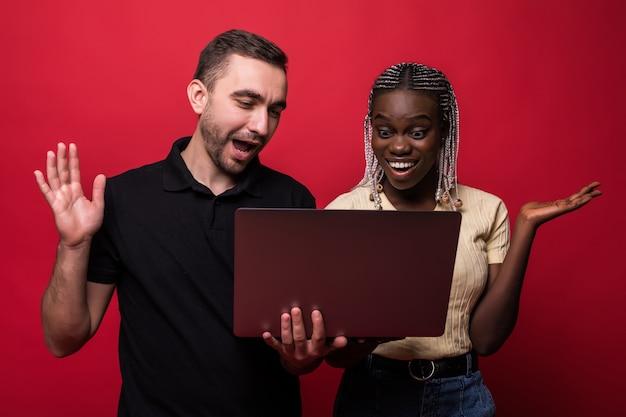 Jonge gemengd ras paar blanke man en afrikaanse vrouw hoding en met behulp van laptop staande geïsoleerd op rode achtergrond