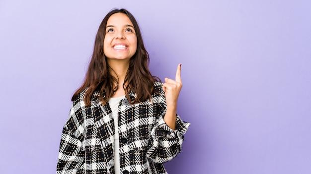 Jonge gemengd ras spaanse vrouw geïsoleerd geeft aan met beide vingers omhoog met een lege ruimte.