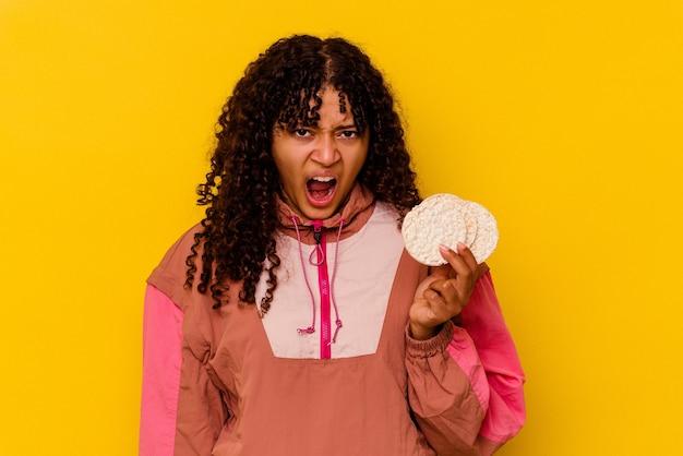 Jonge gemengd ras sport vrouw met een rijstwafel geïsoleerd op geel schreeuwen erg boos en agressief.