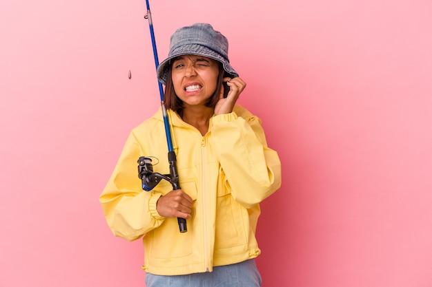 Jonge gemengd ras vrouw beoefenen van vissen geïsoleerd op roze achtergrond die betrekking hebben op oren met handen.