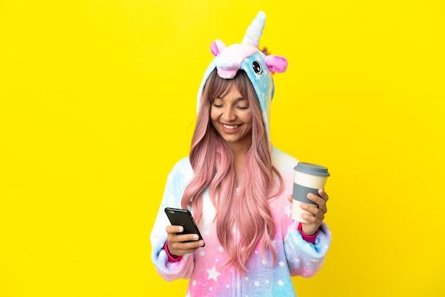 Jonge gemengd ras vrouw draagt een eenhoorn pyjama geïsoleerd op een witte achtergrond met koffie om mee te nemen en een mobiel