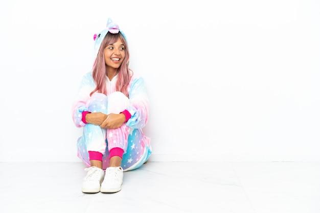 Jonge gemengd ras vrouw draagt een eenhoorn pyjama zittend op de vloer geïsoleerd op een witte achtergrond gelukkig en glimlachend