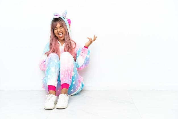 Jonge gemengd ras vrouw draagt een eenhoorn pyjama zittend op de vloer geïsoleerd op een witte achtergrond gitaar gebaar maken