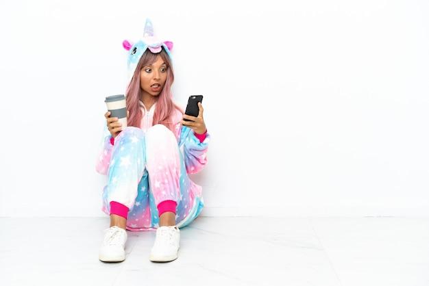 Jonge gemengd ras vrouw draagt een eenhoorn pyjama zittend op de vloer geïsoleerd op een witte achtergrond met koffie om mee te nemen en een mobiel