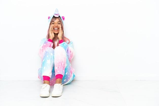 Jonge gemengd ras vrouw draagt een eenhoorn pyjama zittend op de vloer geïsoleerd op een witte achtergrond schreeuwen en iets aankondigen