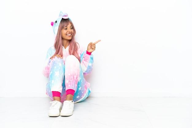 Jonge gemengd ras vrouw draagt een eenhoorn pyjama zittend op de vloer geïsoleerd op een witte achtergrond wijzende vinger naar de zijkant en presenteren van een product