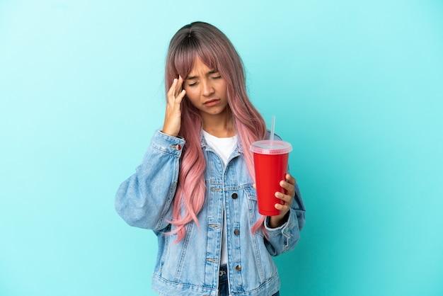 Jonge gemengd ras vrouw drinken van een vers drankje geïsoleerd op blauwe achtergrond met hoofdpijn