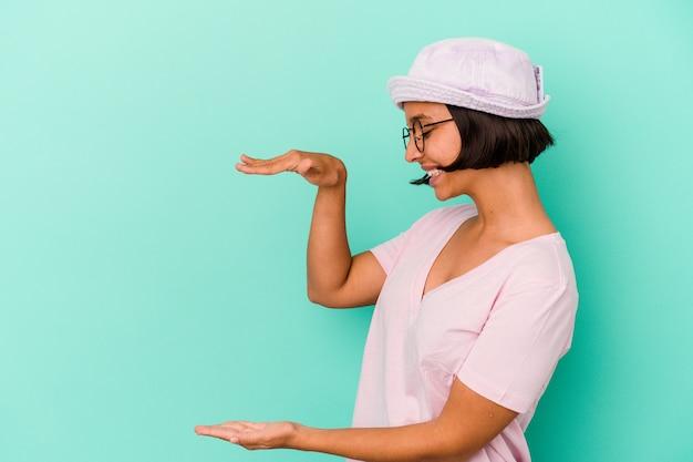 Jonge gemengd ras vrouw geïsoleerd op blauwe achtergrond geschokt en verbaasd met een kopie ruimte tussen handen.