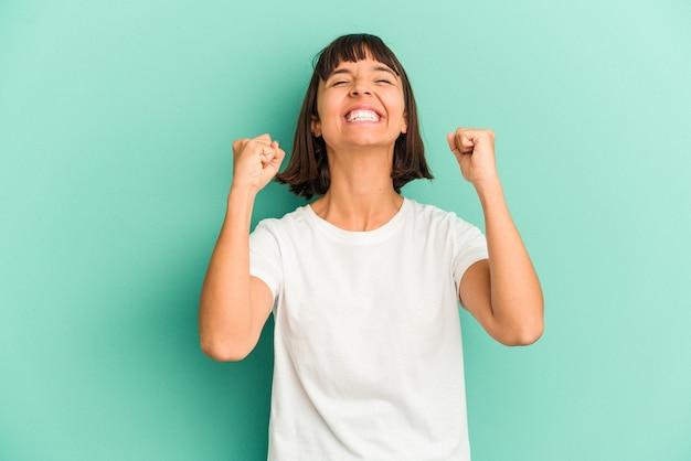 Jonge gemengd ras vrouw geïsoleerd op blauwe achtergrond geschokt, mond bedekken met handen, angstig om iets nieuws te ontdekken.