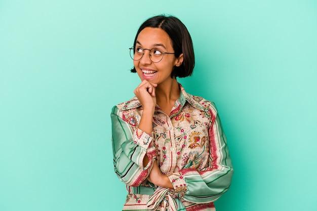 Jonge gemengd ras vrouw geïsoleerd op blauwe achtergrond glimlachend gelukkig en zelfverzekerd, kin met de hand aan te raken.