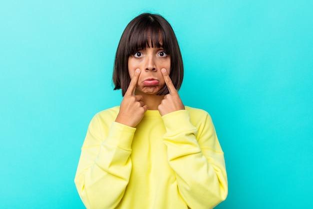 Jonge gemengd ras vrouw geïsoleerd op blauwe achtergrond huilen, ongelukkig met iets, pijn en verwarring concept.