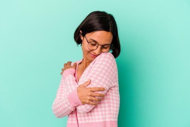 Jonge gemengd ras vrouw geïsoleerd op blauwe achtergrond knuffels, zorgeloos en gelukkig glimlachen.