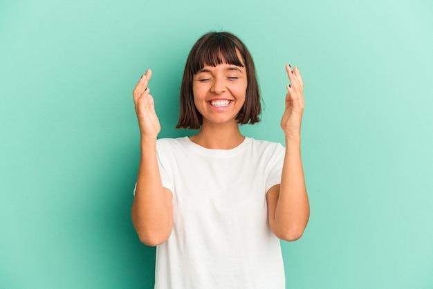 Jonge gemengd ras vrouw geïsoleerd op blauwe achtergrond lachen houden handen op het hart, concept van geluk.