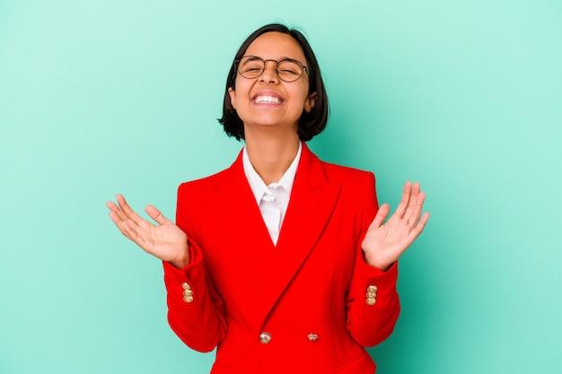 Jonge gemengd ras vrouw geïsoleerd op blauwe achtergrond lacht hardop met de hand op de borst.
