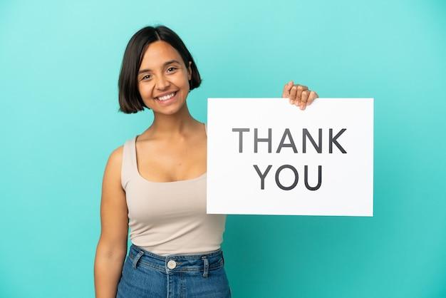 Jonge gemengd ras vrouw geïsoleerd op blauwe achtergrond met een bordje met tekst dank u met gelukkige uitdrukking