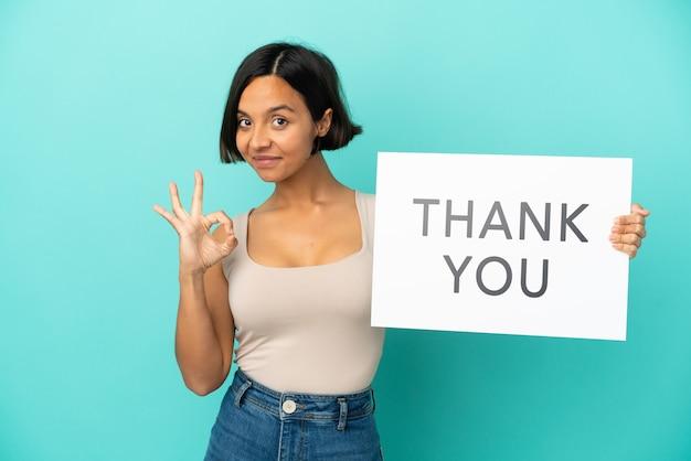 Jonge gemengd ras vrouw geïsoleerd op blauwe achtergrond met een bordje met tekst dank u met ok teken