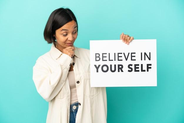 Jonge gemengd ras vrouw geïsoleerd op blauwe achtergrond met een bordje met tekst geloof in je zelf en denken