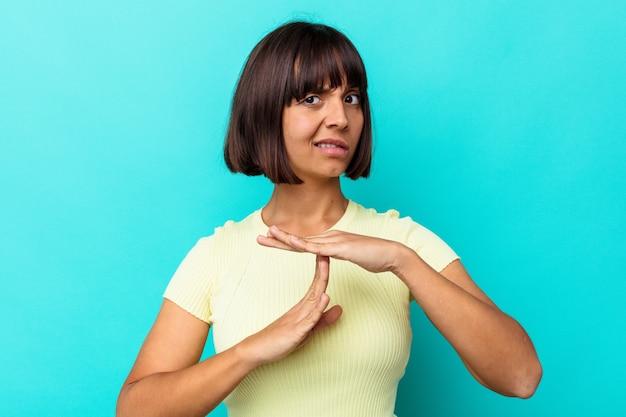 Jonge gemengd ras vrouw geïsoleerd op blauwe achtergrond met een time-out gebaar.