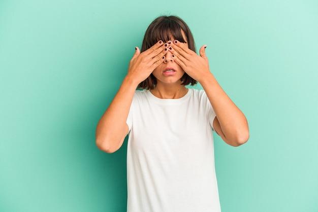 Jonge gemengd ras vrouw geïsoleerd op blauwe achtergrond met hoofdpijn, voorkant van het gezicht aan te raken.