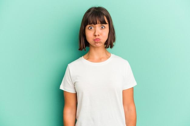 Jonge gemengd ras vrouw geïsoleerd op blauwe achtergrond ongelukkig in de camera kijken met sarcastische uitdrukking.