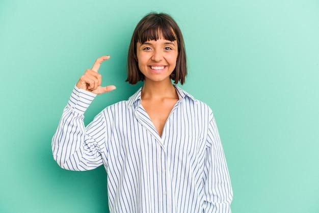 Jonge gemengd ras vrouw geïsoleerd op blauwe achtergrond ontvangen een aangename verrassing, opgewonden en handen opsteken.