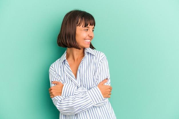 Jonge gemengd ras vrouw geïsoleerd op blauwe achtergrond punten met duim vinger weg, lachen en zorgeloos.