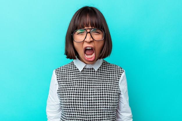 Jonge gemengd ras vrouw geïsoleerd op blauwe achtergrond schreeuwen erg boos, woede concept, gefrustreerd.