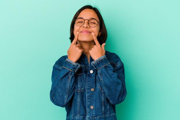 Jonge gemengd ras vrouw geïsoleerd op blauwe achtergrond twijfelen tussen twee opties.