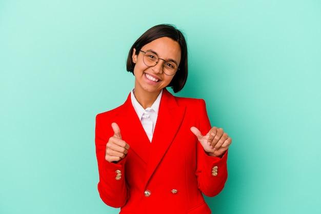 Jonge gemengd ras vrouw geïsoleerd op blauwe achtergrond verhogen beide duimen omhoog, glimlachend en zelfverzekerd.