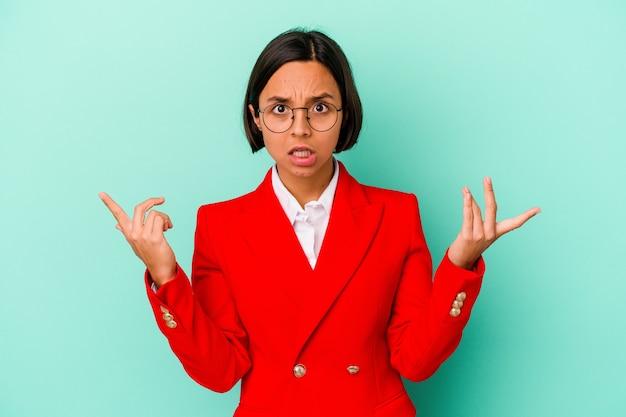 Jonge gemengd ras vrouw geïsoleerd op blauwe achtergrond wijzend naar verschillende kopieerruimten, een van hen kiezen, tonen met vinger.
