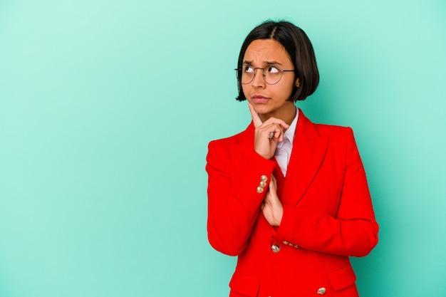 Jonge gemengd ras vrouw geïsoleerd op blauwe achtergrond zijwaarts kijkend met twijfelachtige en sceptische uitdrukking.