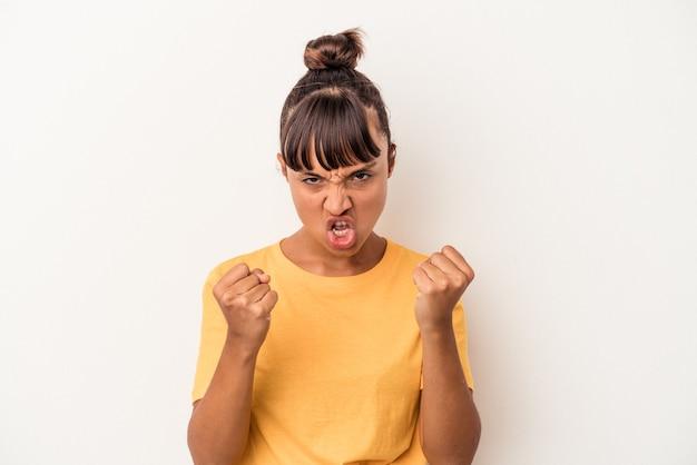 Jonge gemengd ras vrouw geïsoleerd op een witte achtergrond boos schreeuwen met gespannen handen.
