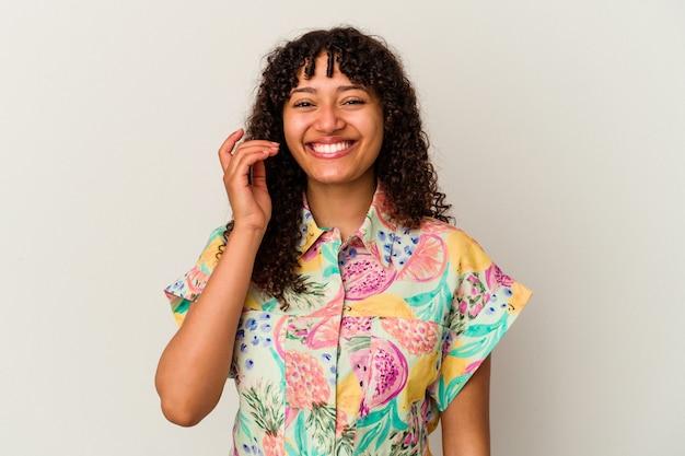 Jonge gemengd ras vrouw geïsoleerd op een witte achtergrond lachen om iets, mond bedekken met handen.
