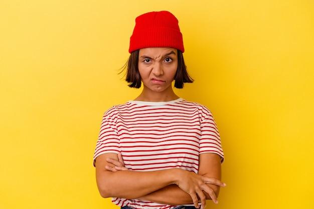 Jonge gemengd ras vrouw geïsoleerd op gele achtergrond fronsend gezicht in ongenoegen, houdt armen gevouwen.