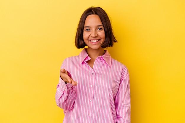 Jonge gemengd ras vrouw geïsoleerd op gele achtergrond hand uitrekken op camera in begroeting gebaar.