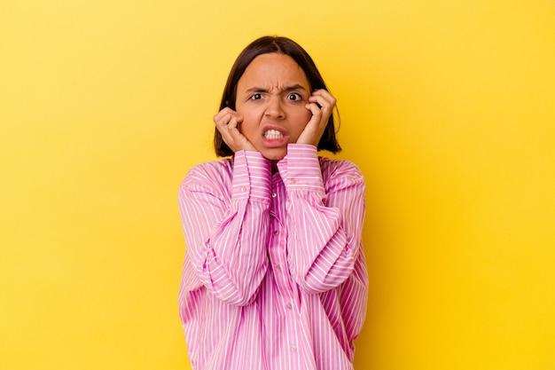 Jonge gemengd ras vrouw geïsoleerd op gele achtergrond huilen, ongelukkig met iets, pijn en verwarring concept.