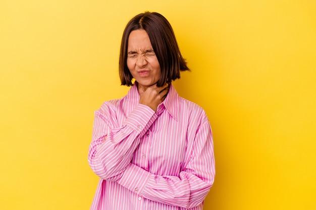 Jonge gemengd ras vrouw geïsoleerd op gele achtergrond lijdt aan pijn in de keel als gevolg van een virus of infectie.
