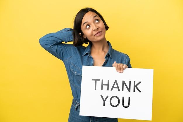 Jonge gemengd ras vrouw geïsoleerd op gele achtergrond met een bordje met de tekst dank u en denken