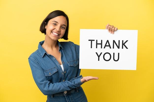 Jonge gemengd ras vrouw geïsoleerd op gele achtergrond met een bordje met de tekst dank u en erop te wijzen