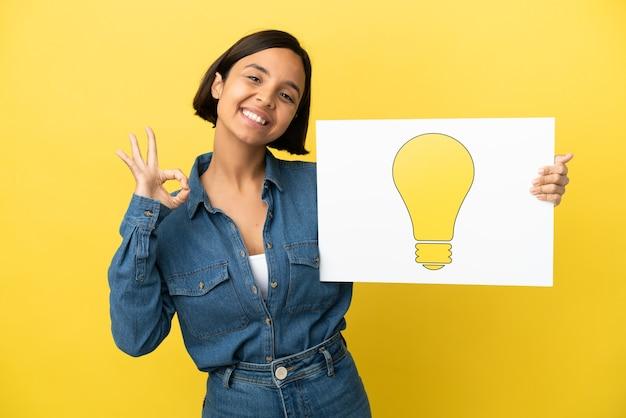 Jonge gemengd ras vrouw geïsoleerd op gele achtergrond met een bordje met lamp icoon met ok teken
