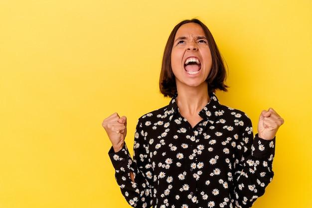 Jonge gemengd ras vrouw geïsoleerd op gele achtergrond schreeuwen erg boos, woede concept, gefrustreerd.