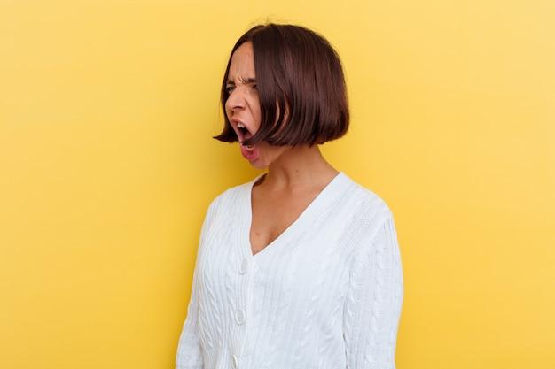Jonge gemengd ras vrouw geïsoleerd op gele achtergrond schreeuwen naar een kopie ruimte