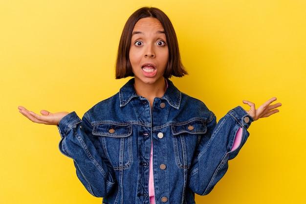 Jonge gemengd ras vrouw geïsoleerd op gele achtergrond twijfelen en schouders ophalen in ondervraging gebaar.