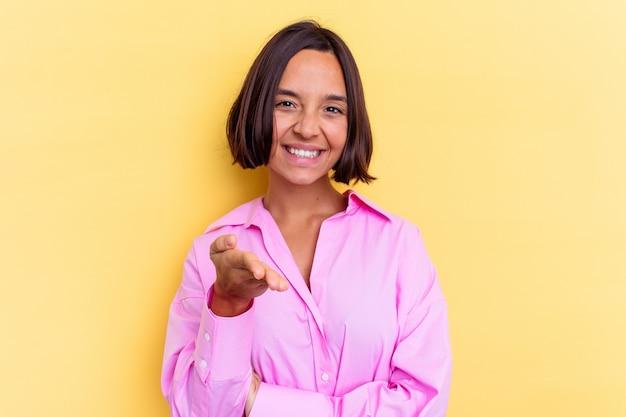Jonge gemengd ras vrouw geïsoleerd op gele achtergrond uitrekkende hand op camera in groetgebaar.